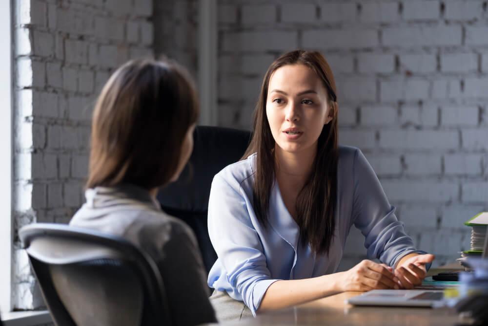 comunicaçao entre duas mulheres em escritorio