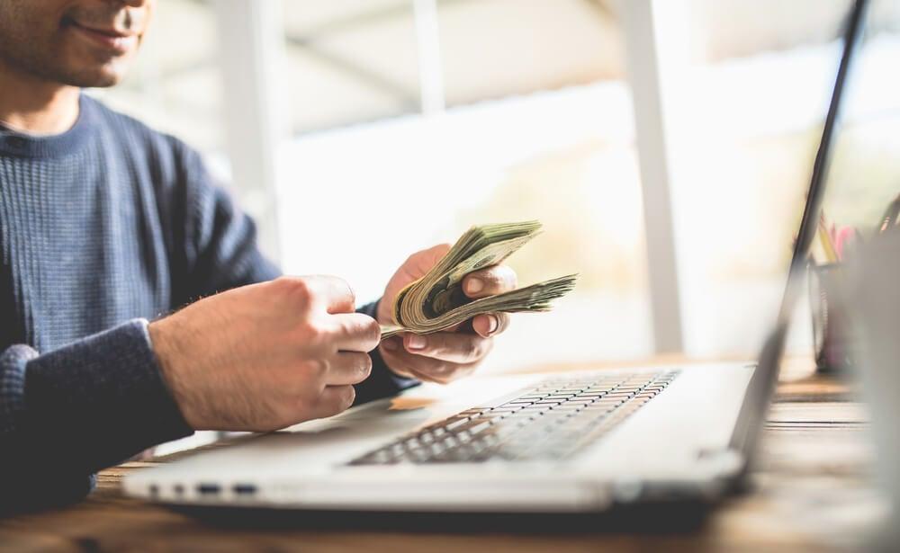 digital influencer segurando notas de dinheiro em frente a um laptop