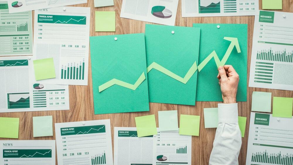 documentos com gráficos e dados executivos em papéis verdes