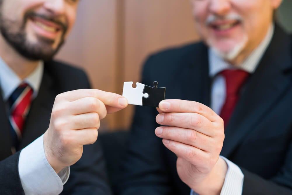 dois profissionais executivos juntando peças de quebra cabeça representando fusão de empresas