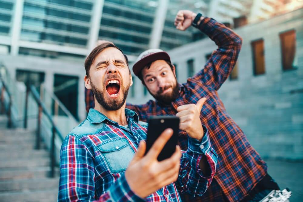 dupla de amigos comemorando algo visto em smartphone