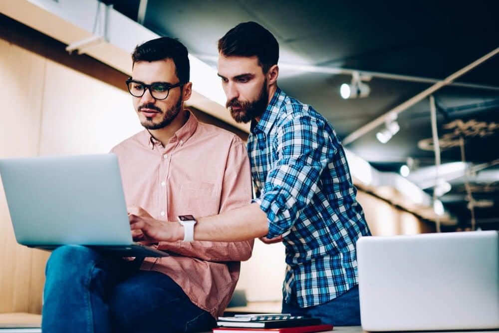 dupla de colegas de trabalho se ajudando em trabalho em laptop