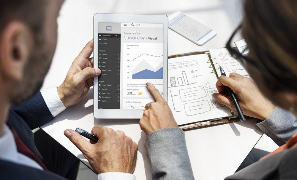 dupla de profissionais analisando dados de planejamento estratégico em tablet