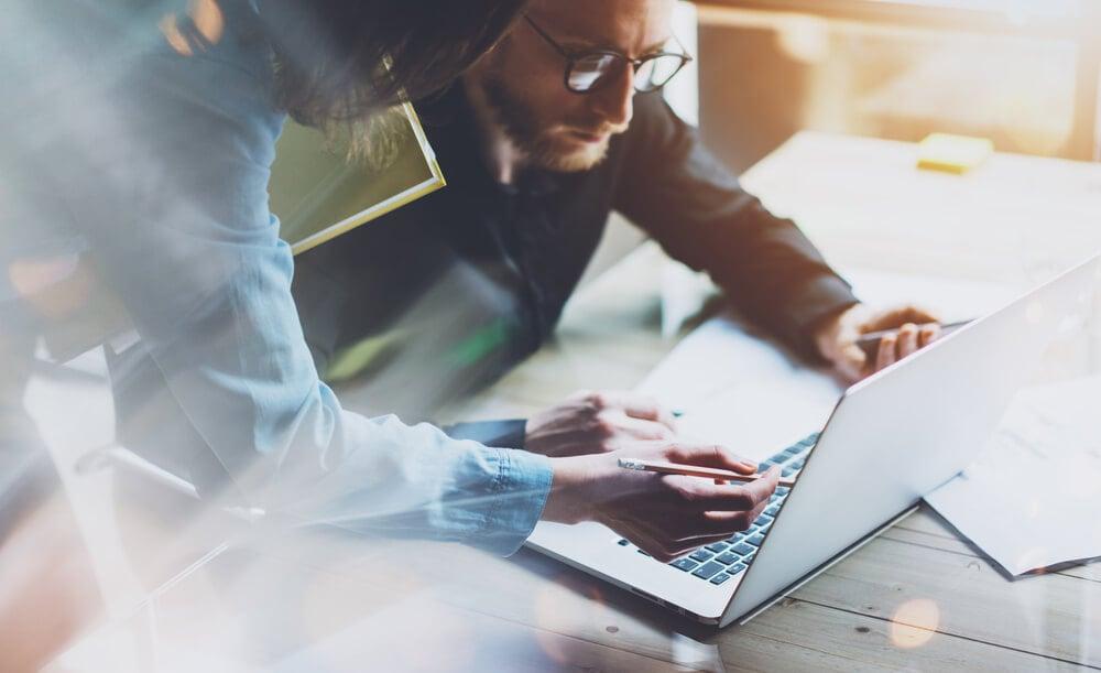 dupla de profissionais trabalhando em modelo de negocio em frente a laptop