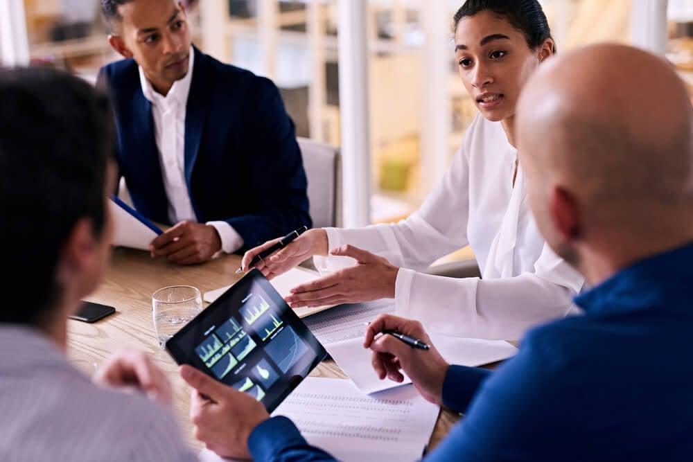 equipe analisando gráficos de crescimento em mesa de reuniões