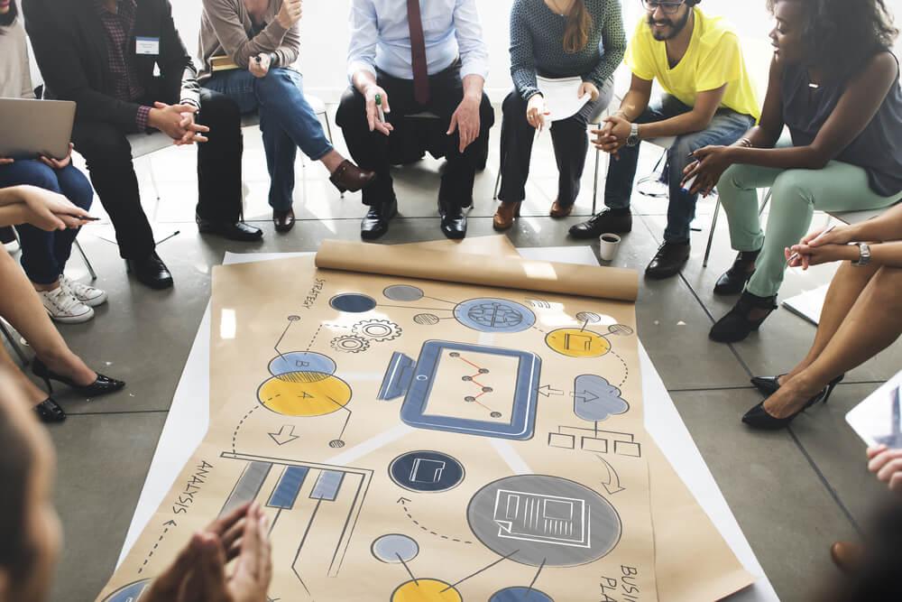 equipe de trabalho em volta de ilustrações de dados