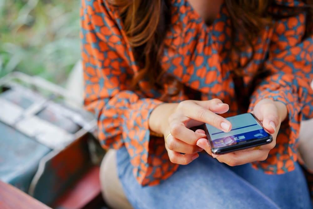 garota acessando o app mobile do facebook em smartphone