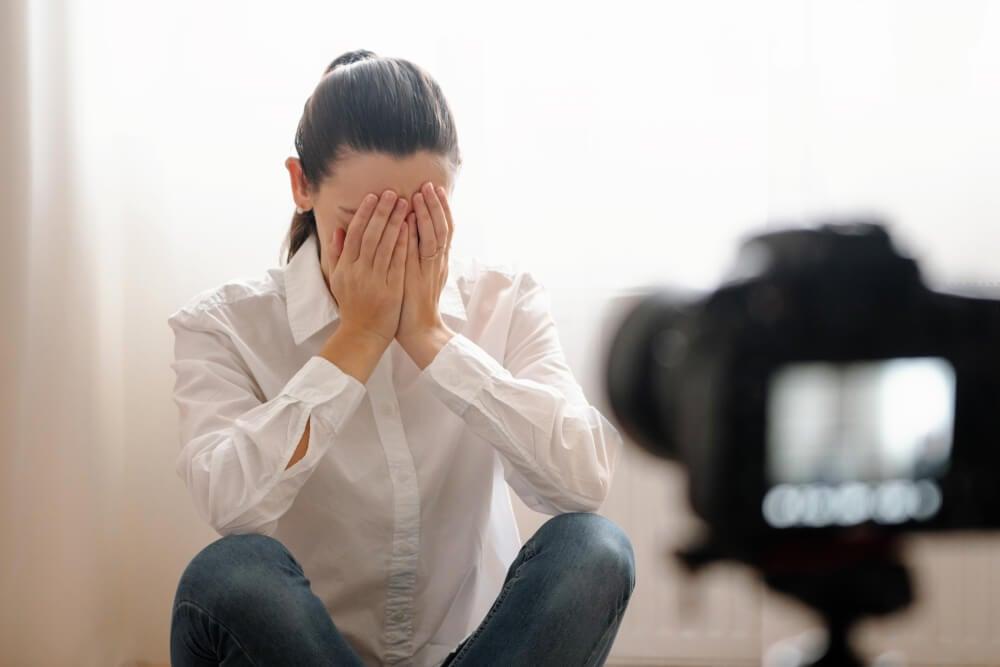 garota com gestos de tristeza em frente a camera