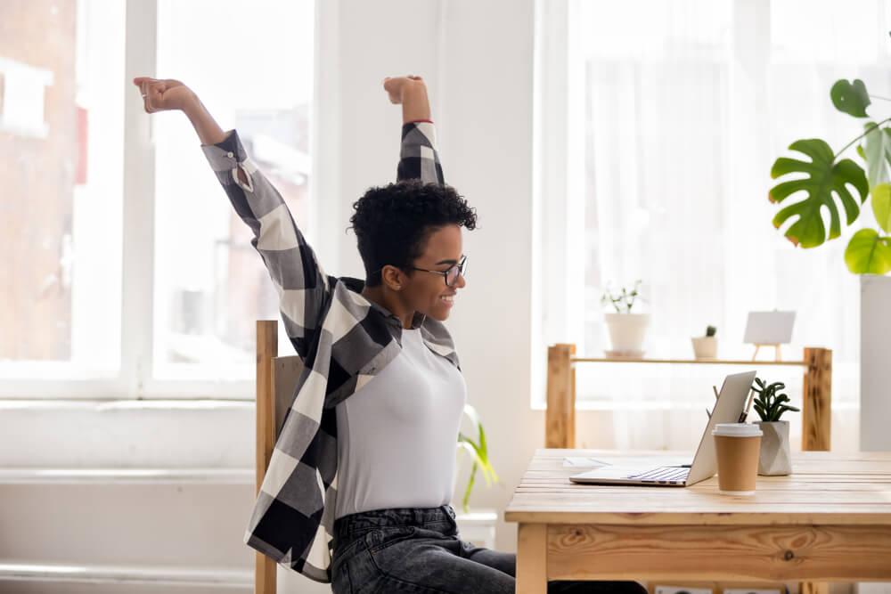 garota comemorando algo em frente a laptop com braços para cima