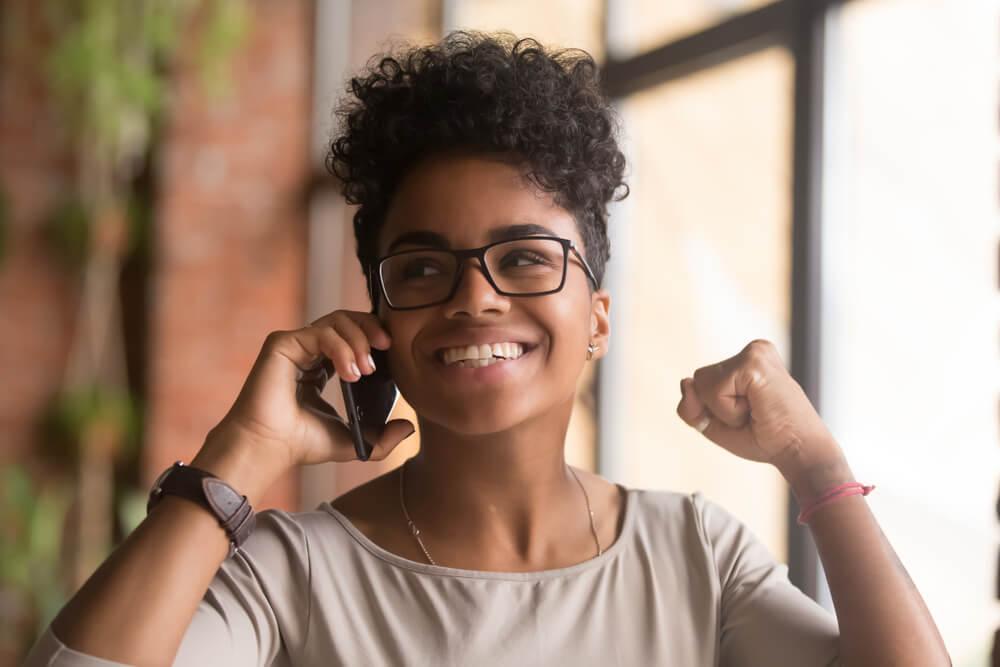 garota feliz recebdno contato de empresa por telefone no processo de pós venda