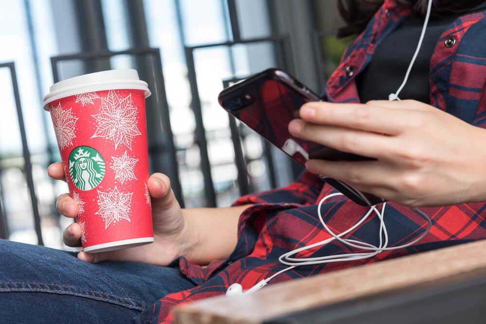 garota segurando copo da empresa starbucks enquanto acessa smartphone