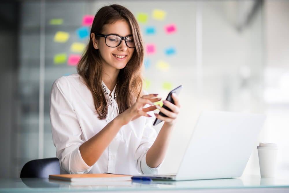 garota segurando smartphone em mesa executiva com laptop e sua frente