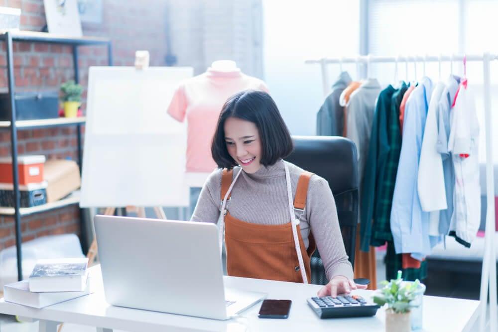 garota sorridente trabalhando com vendas online