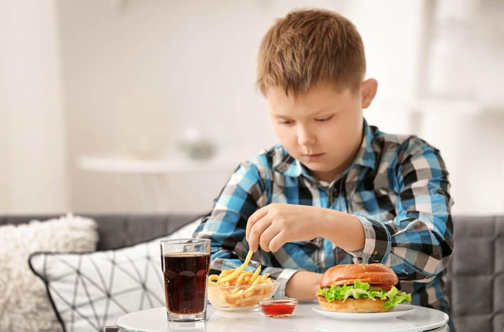 garotinho consumindo alimentos industrializados