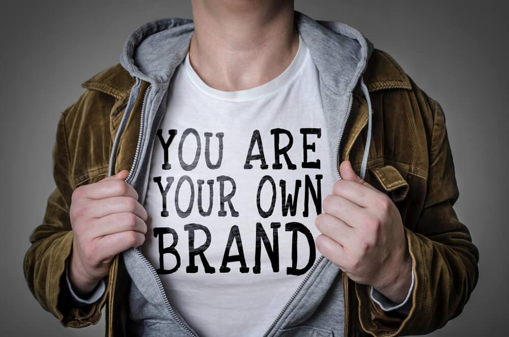 """garoto mostrando camiseta com frase """"eu sou sua própria marca"""""""