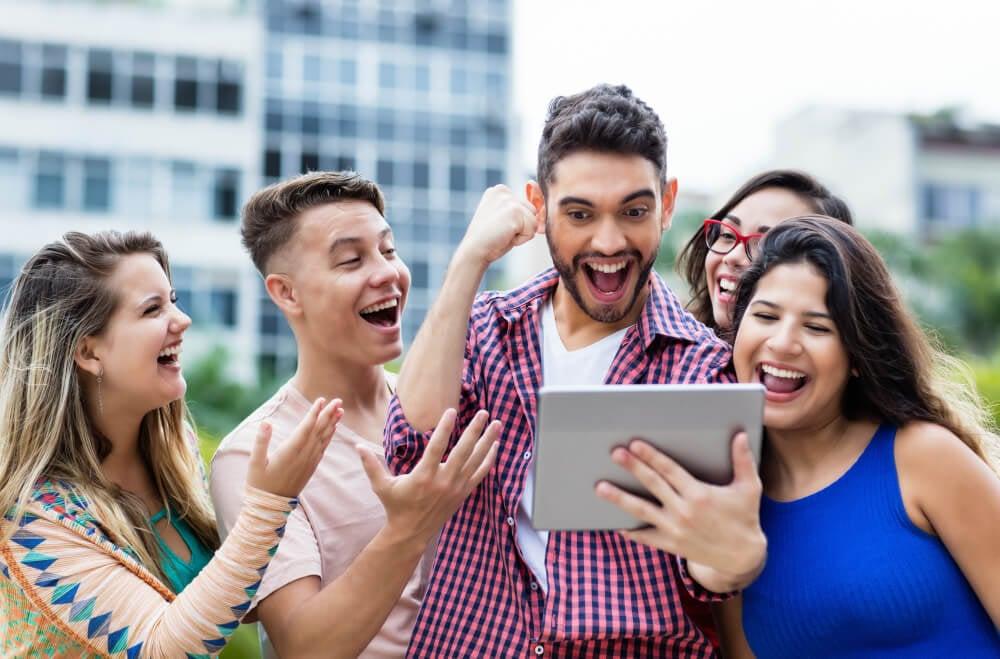 grupo de amigos comemorando vitória em sorteio virtual visto em tablet