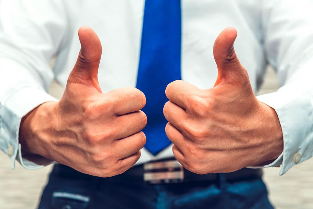 homem com vestes executiva fazendo sinais positivios com as mãos