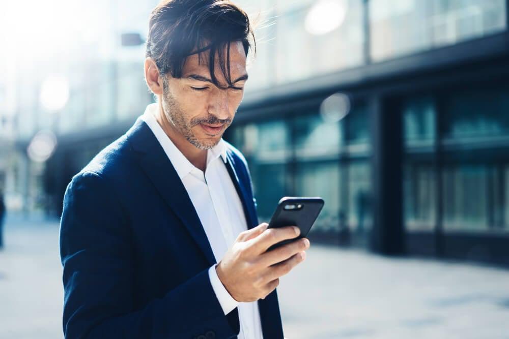 homem de negocios acessando smartphone