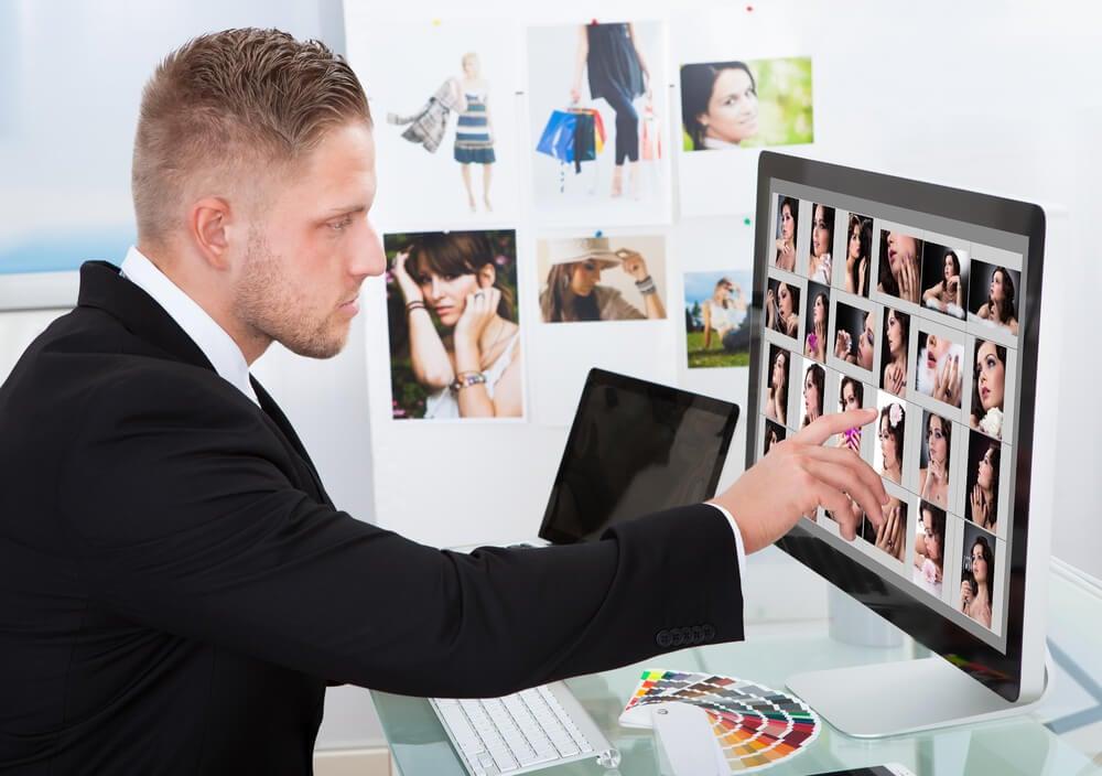 homem de terno apontando foto em banco de imagens apresentado em tela de desktop