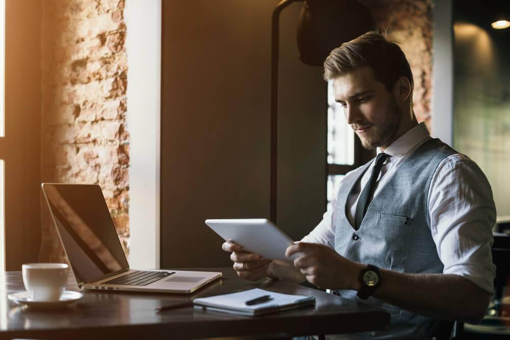 homem de vestes sociais acessando tablet em mesa informal de café