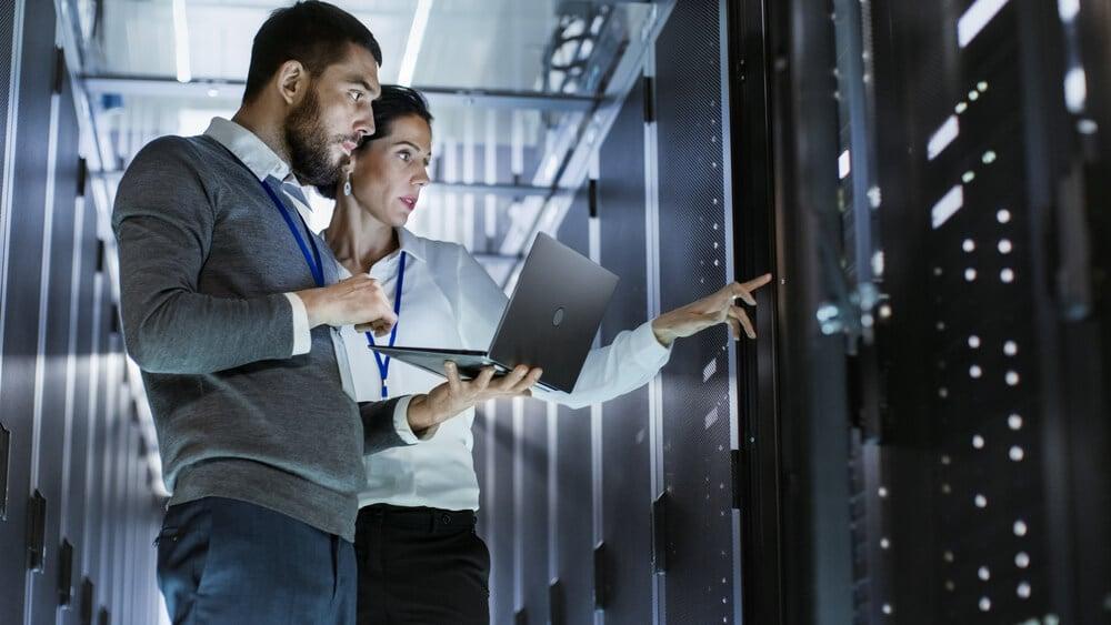 homem e mulher profissionais da area de tecnologia segurando laptop