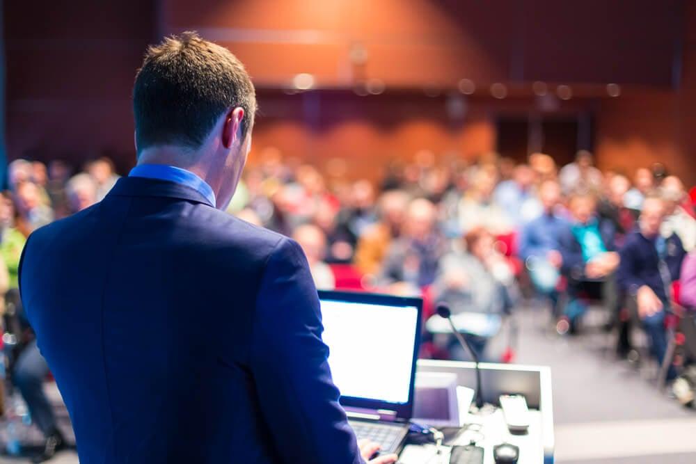 homem em frente a um laptop dando uma palestra