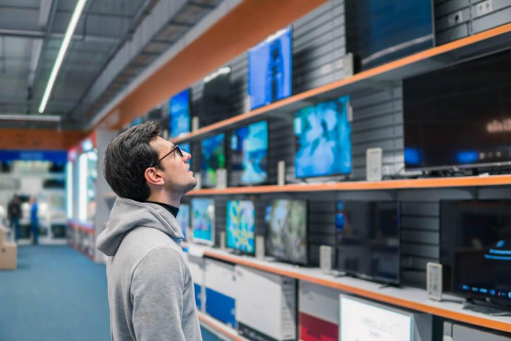 homem em loja física em processo de decisão de compra de uma TV