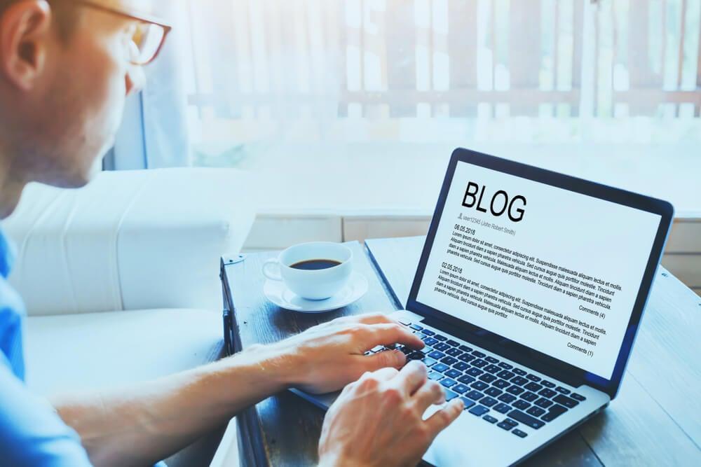 homem em mesa rustica com laptop em sua frente com pagina de texto de blog em tela
