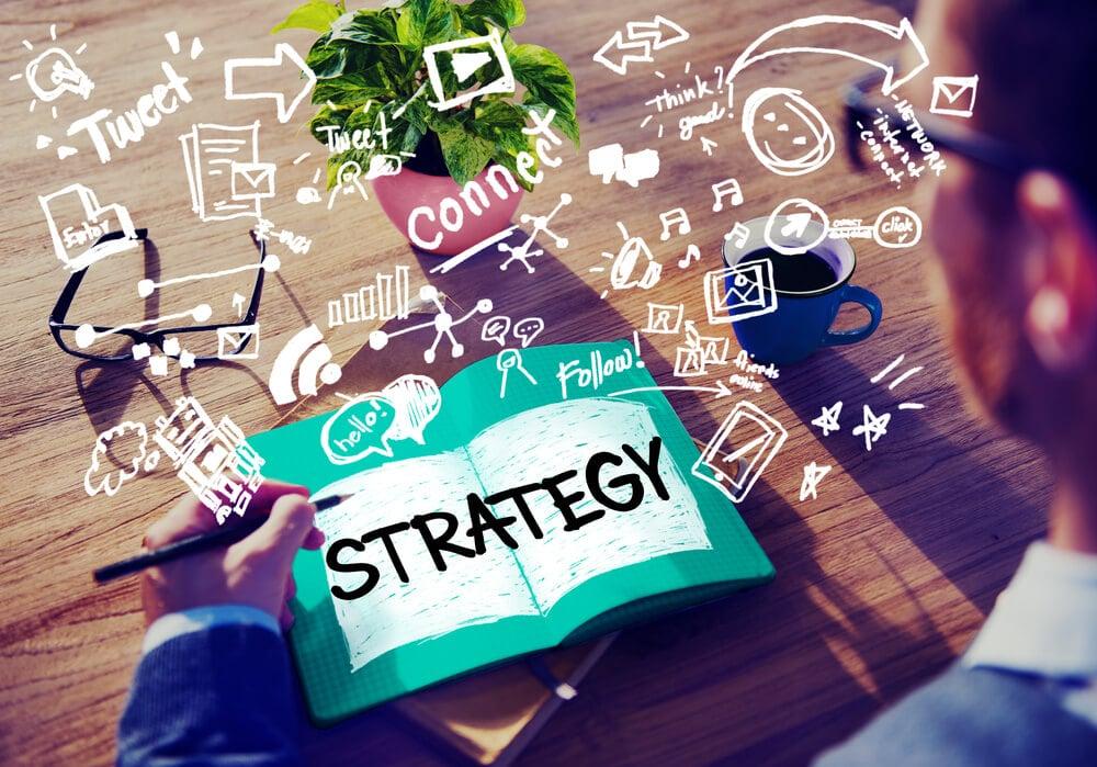 homem escrevendo em caderno e ilustrações sobre estratégia