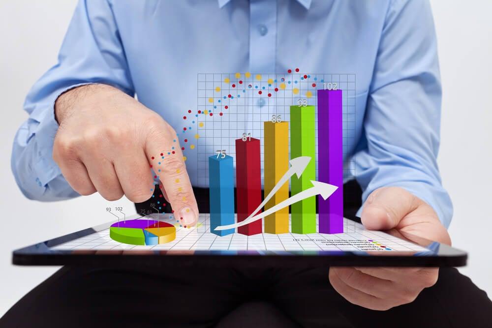 homem executivo assinalando sob tablet símbolos em 3d de negócios e gráficos