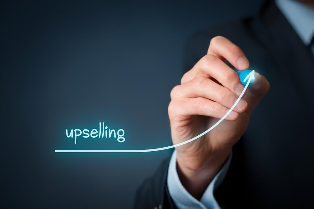 homem executivo desenhando seta aumentando com a palavra upselling em destaque