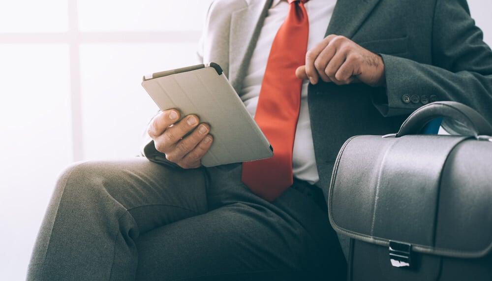 homem executivo segurando tablet com maleta ao lado