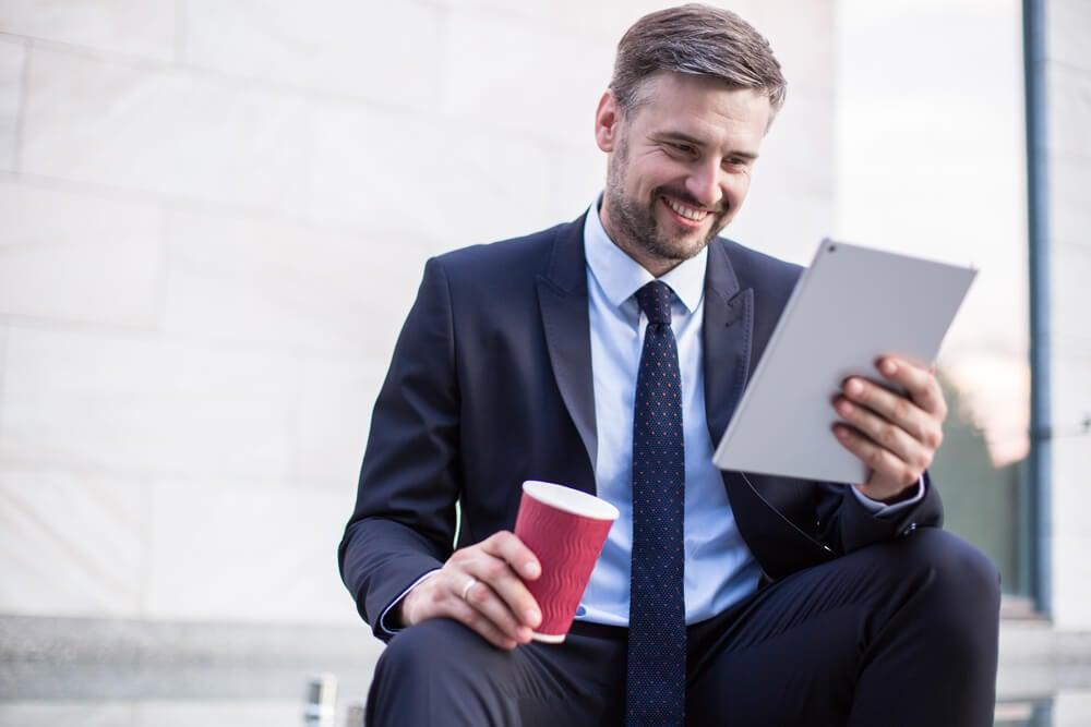 homem executivo sorridente olhando para tablet