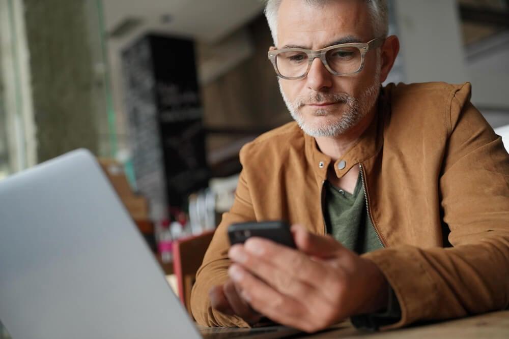 homem maduro em frente a laptop e acessando smartphone