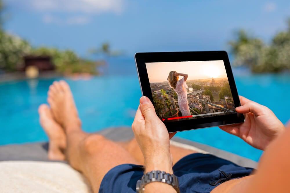 homem na praia segurando um tablet