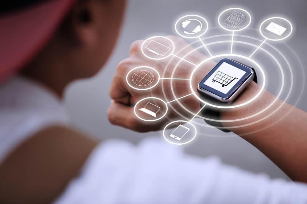 homem olhando em relógio inteligente com símbolo de compras e outros relacionados a dispositivos