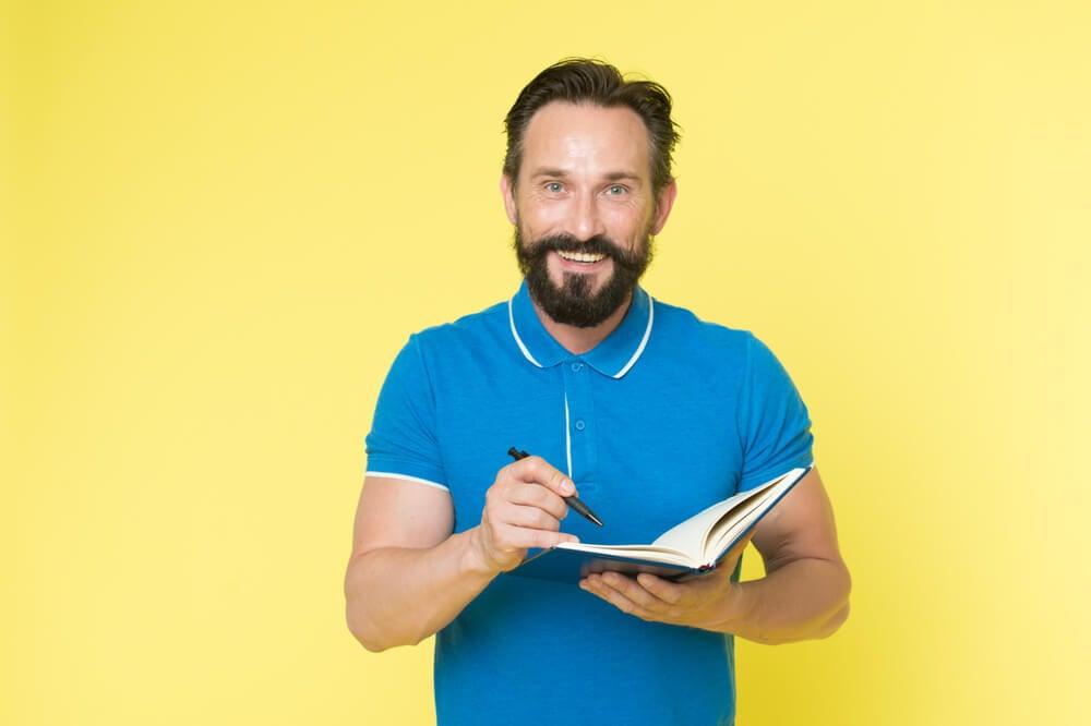 homem segurando agenda de anotações sorridente