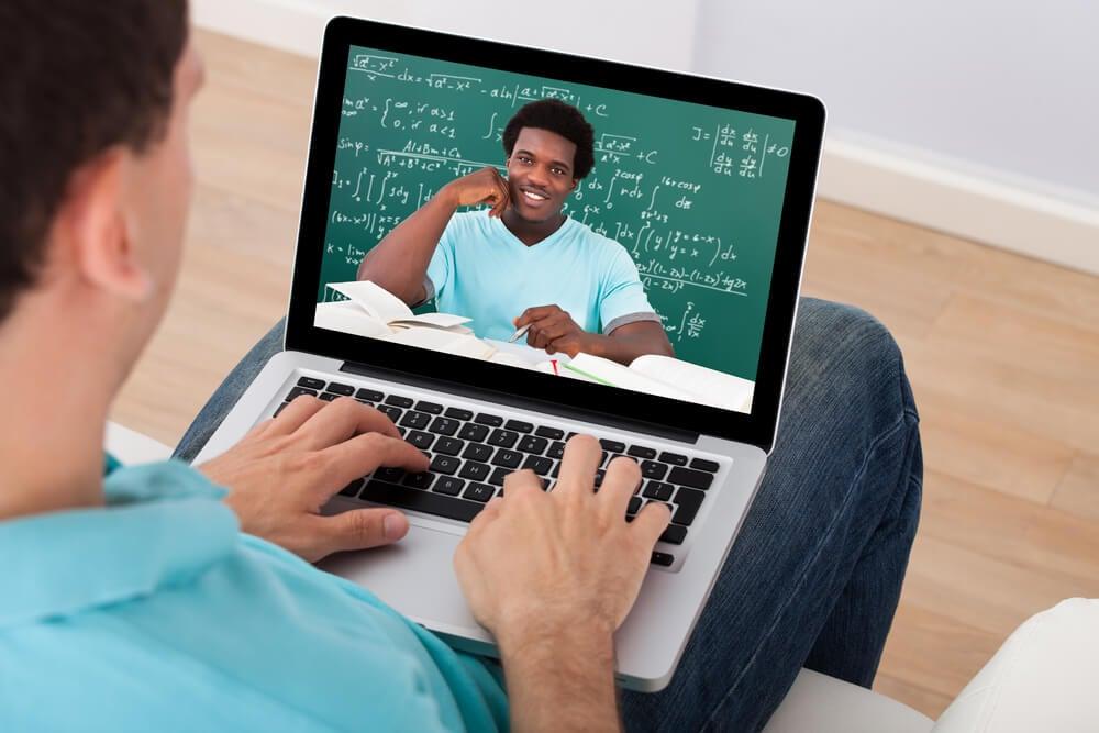 homem segurando laptop assistndo a um curso online