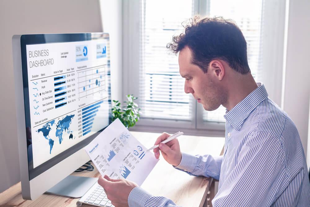 homem segurando papel em frente a computador com ticket medio