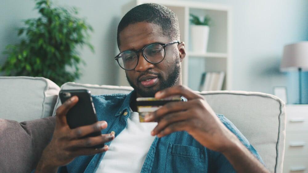 homem segurando smartphone e cartão de crédito
