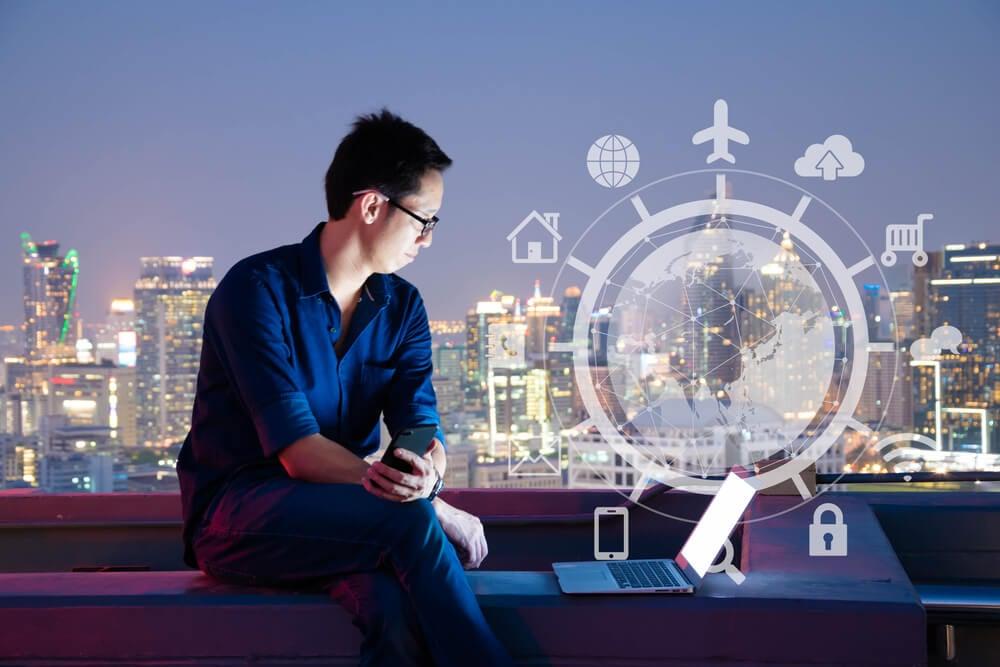homem sentado segurando smartphone em cenário com fundo de cidade observando símbolos da era digital