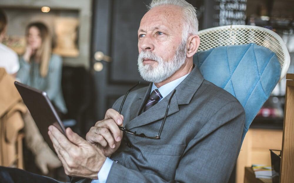 homem sério em contato com a era digital por meio de um tablet