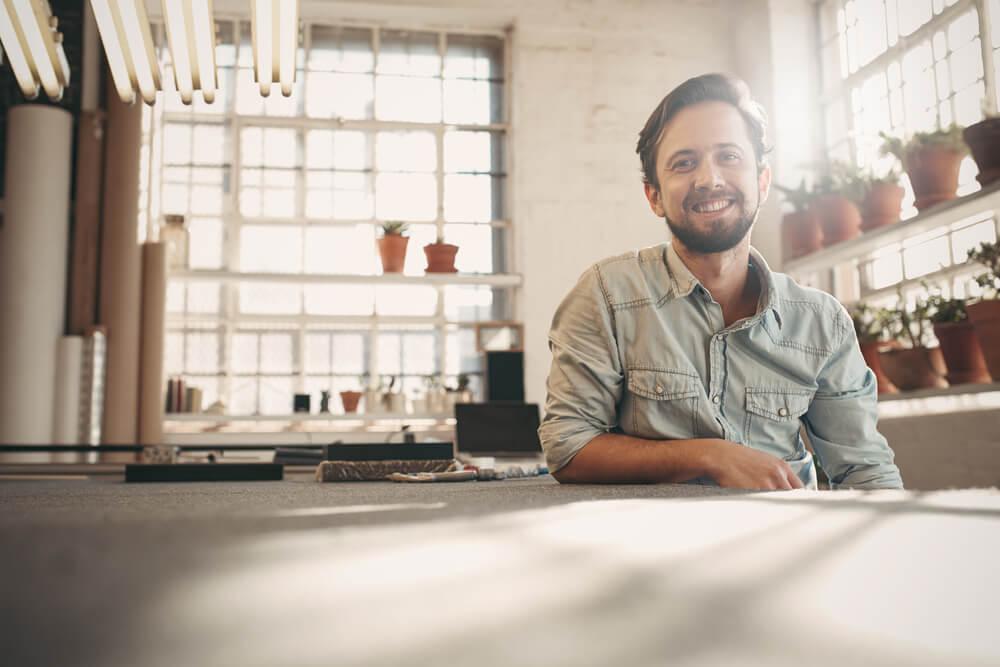homem sorridente em pequeno negócio