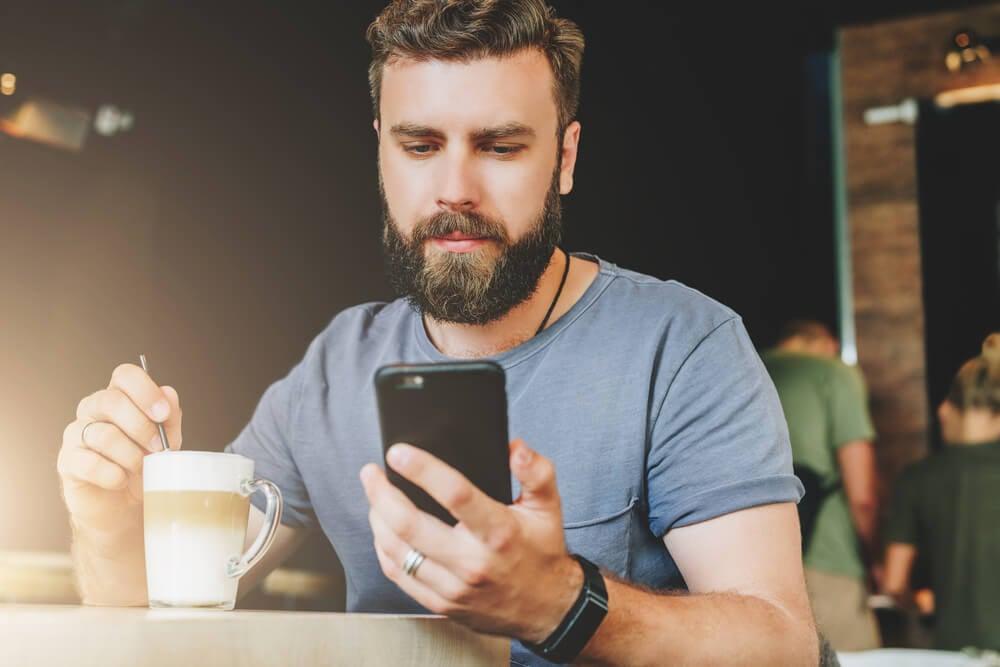 homem tomando café acessando smartphone