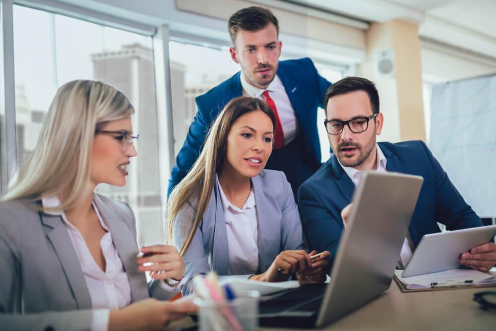 homens e mulheres focados em laptop trabalhando em relaçoes publicas