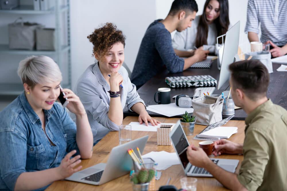 homens e mulheres trabalhando juntos em relaçoes publicas com laptops e materiais de escritorio