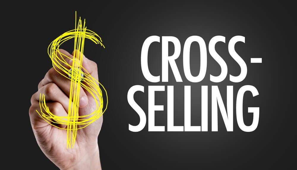 ilustraçao da palavra cross selling com mao desenhando sinal de capital