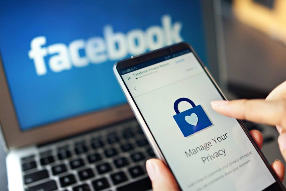 laptop com acesso ao facebook e smartphone em página de privacidade do app mobile