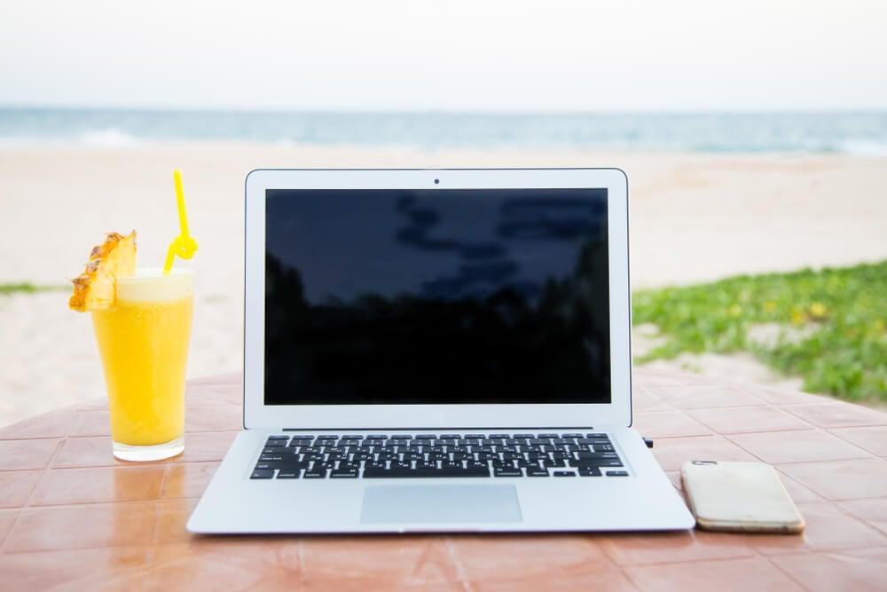 laptop com copo ao lado em cenario de praia