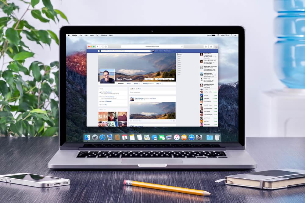 laptop em mesa junto de caderno de anotações acessando a fanpage no facebook